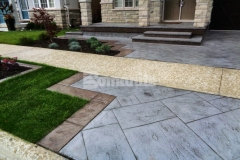 Bomanite Shale Gray Color Hardener and a Gray Release Agent were paired here with the Bomanite Yorkshire Stone imprint pattern to create a decorative concrete driveway and patio that complement the existing concrete walkway and add distinctive design detail that enhances the home's architecture.