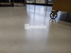 Close up of shiny flooring at the flagship store of Nickel & Suede using Bomanite Modena SL Custom Polished decorative concrete overlay installed by Musselman & Hall Contractors, LLC in Kansas City, MO.