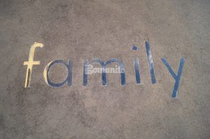 """Word """"Family"""" in metal letters embedded in decorative concrete consisting of Bomanite Sandscape Texture Exposed Aggregate Systems at Tulsa Family Center for Juvenile Justice in Tulsa, OK, installed by Bomanite of Tulsa."""