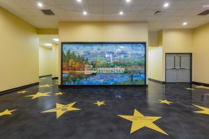 Lobby view of wall art and donor stars in decorative concrete flooring at the Jaffrey Park Theatre in Jaffrey, NH, with a sleek dark Bomanite Renaissance Polished Concrete Floor as the background to the Golden Stars engraved with donor names in brilliant blue created with the Bomanite Modena TG system installed by Bomanite Licensee Premier Concrete Construction.