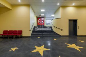Stairway to red doors from lobby featuring a sleek dark Bomanite Renaissance Polished Concrete Floor as the background ans Golden Stars engraved with donor names in brilliant blue created with the Bomanite Modena TG system at Jaffrey Park Theatre in Jaffrey, NH, installed by Bomanite Licensee Premier Concrete Construction.